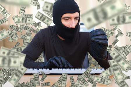 thievery: Burglar with balaclava hacking a laptop against light shining into living room