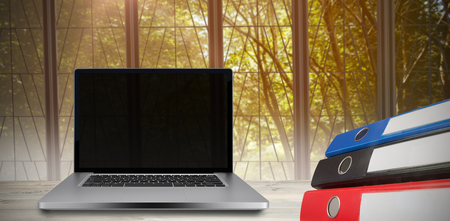 bulding: Desk with laptop against view of a tree
