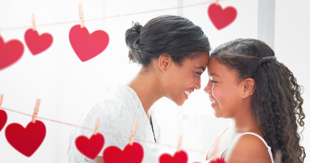 Composite image of mother and daughter looking each other behind a heart tinsel Stock Photo