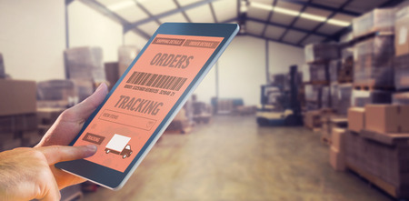 Man using tablet pc against forklift in a large warehouse Reklamní fotografie