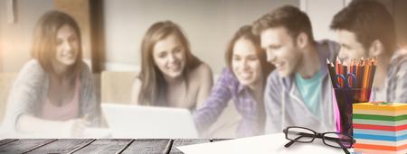 woman laptop: School supplies on desk against smiling friends students using laptop