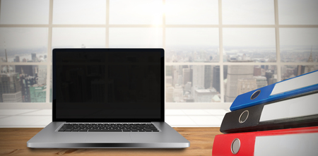 city view: Desk with laptop against view of a city