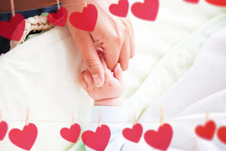 Hearts hanging on a line against a mother holding her baby hand photo
