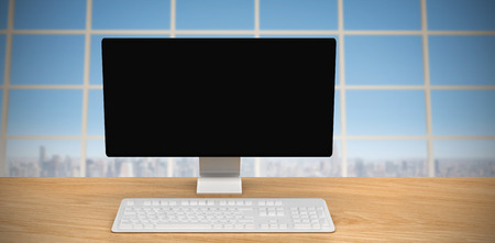 overlooking: A computer over a desk  against view over city Stock Photo