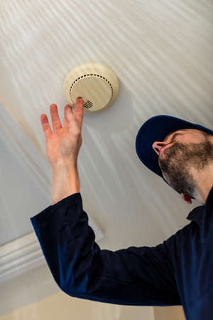 detector: Handyman installing smoke detector on the ceiling