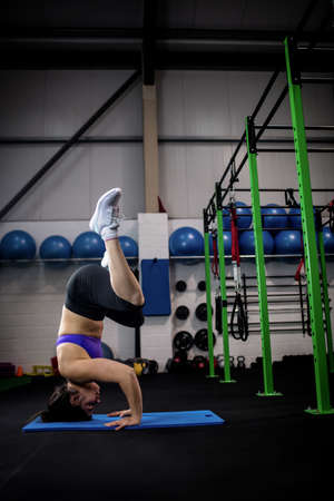 headstand: Side view of a woman performing a headstand on mat at gym LANG_EVOIMAGES