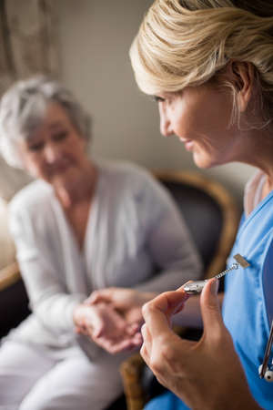 career timing: Nurse taking care of a senior woman in a retirement home LANG_EVOIMAGES