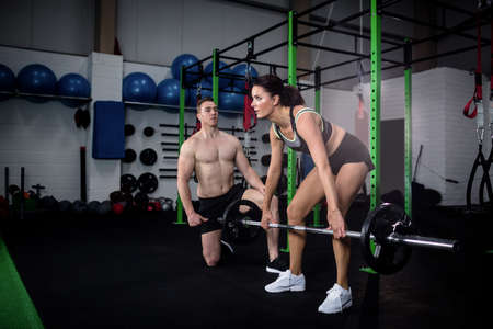 instructing: Trainer instructing a woman while lifting barbell at gym