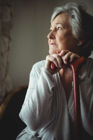 sheltered accommodation: Thoughtful senior woman with cane in a retirement home