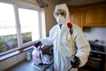 crop sprayer: Pest control man spraying pesticide in kitchen