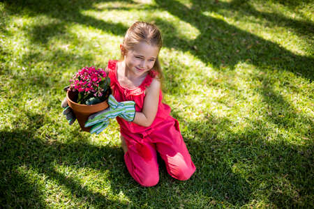 girl holding flower: High angle view of girl holding flower pot while sitting in yard LANG_EVOIMAGES