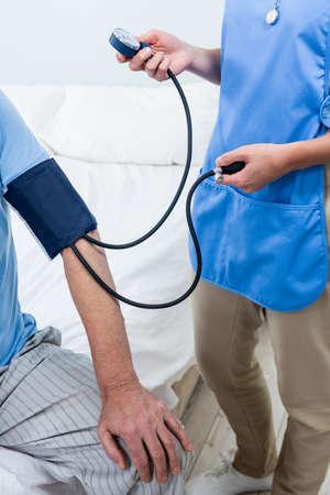 caretaker: Female caretaker checking blood pressure of senior man at hospital