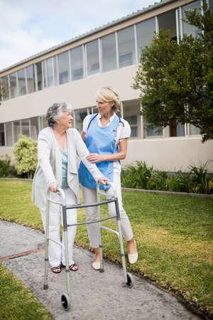 residential tree service: Nurse helping senior woman walking outside the retirement home