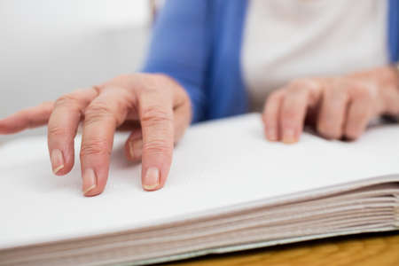 mobility nursing: Blind senior woman using braille to read in a retirement home