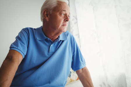 sheltered accommodation: Thoughtful senior man sitting on his bed in a retirement home LANG_EVOIMAGES