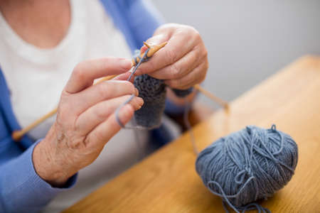 sheltered accommodation: Senior woman knitting in a retirement home