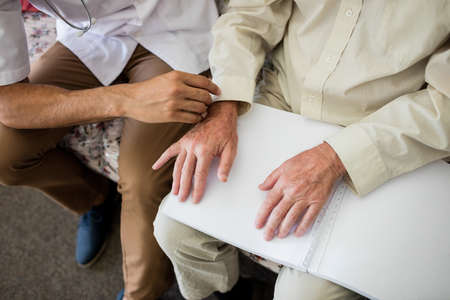 braille: Blind senior man using braille to read in a retirement home LANG_EVOIMAGES