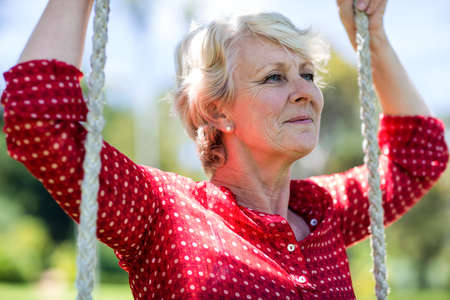 the ageing process: Close-up of a senior woman sitting on a swing in park