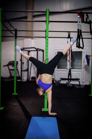 handstand: Woman performing handstand at gym