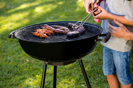 grill tongs sausage: Midsection of boy cooking sausages on barbecue at lawn LANG_EVOIMAGES
