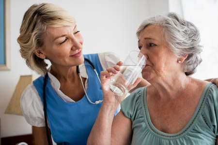 sheltered accommodation: Nurse giving medicaments to a senior woman in a retirement home LANG_EVOIMAGES