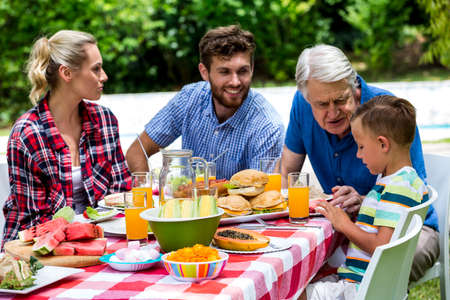 family: Granfather assiting grandson while having lunch at lawn