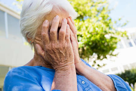 sheltered accommodation: A senior woman hiding her head in a retirement home