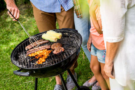 grill tongs sausage: Man preparing food on barbecue grill by family in back yard