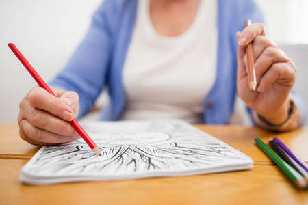 sheltered accommodation: Senior woman colouring in a colouring book in a retirement home LANG_EVOIMAGES