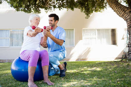exercices: Nurse helping senior woman doing exercises in a retirement home LANG_EVOIMAGES