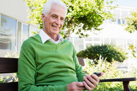 sheltered accommodation: Senior man posing with his smartphone in a retirement home