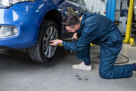 pneumatic: Mechanic fixing a car wheel with pneumatic wrench at the repair garage