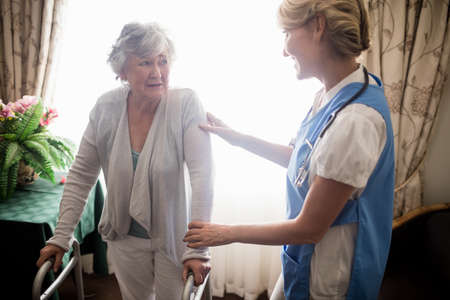 taking care: Nurse taking care of a senior woman in a retirement home LANG_EVOIMAGES