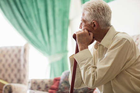 Thoughtful senior man sitting with a cane in a retirement home LANG_EVOIMAGES