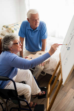 sheltered accommodation: Senior couple painting in a retirement home LANG_EVOIMAGES