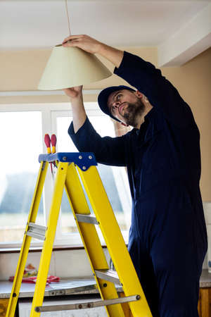 ceiling lamp: Electrician repairing a ceiling lamp at home