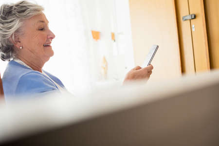 sheltered accommodation: Senior woman using a smartphone in a retirement home LANG_EVOIMAGES