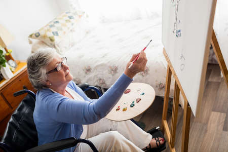 sheltered accommodation: Senior woman painting in a retirement home LANG_EVOIMAGES