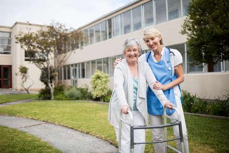 sheltered accommodation: Nurse helping senior woman walking outside the retirement home