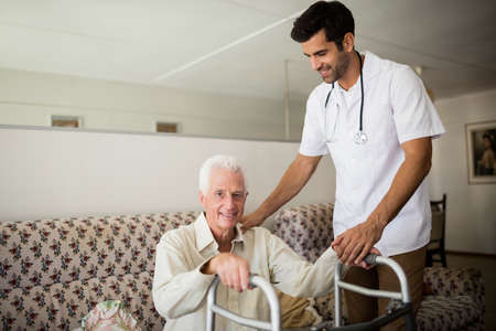 sheltered accommodation: Nurse helping senior man to stand up in a retirement home