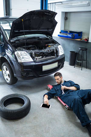 engine bonnet: Mechanic using digital tablet while repairing a car at the repair garage