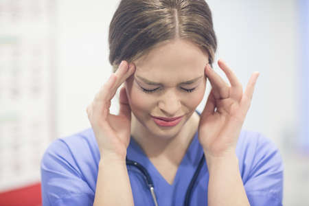 hand on forehead: Stressed vet with hand on forehead in clinic LANG_EVOIMAGES