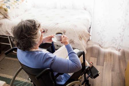 paraplegico: Alto mujer de tomar café en una casa de retiro