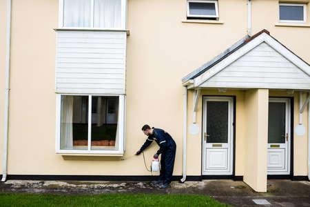 pesticide: Pest control man spraying pesticide outside the house