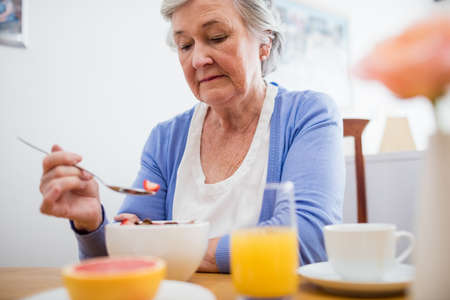 sheltered accommodation: Senior woman having her breakfast in a retirement home