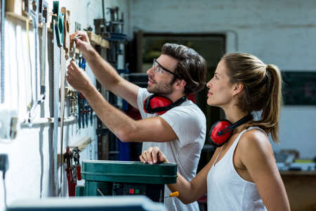 ear muff: Male and female carpenter selecting a tools from hanging bar in workshop LANG_EVOIMAGES