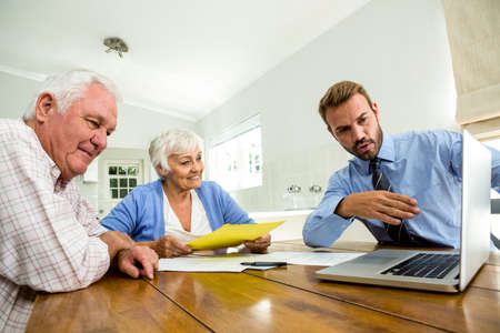 suggesting: Agent suggesting senior couple on laptop at table in house