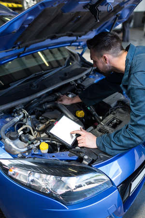 diagnostic tool: Mechanic using a diagnostic tool while examining car engine at the repair garage