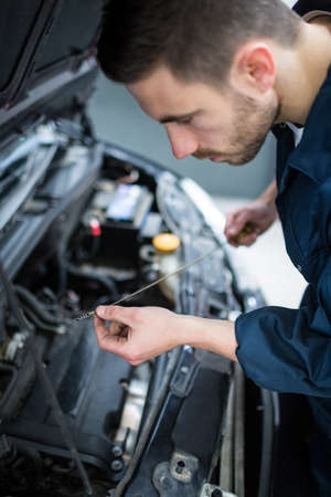 engine bonnet: Mechanic checking the oil level in a car engine with a dipstick at the repair garage LANG_EVOIMAGES