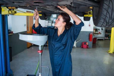 servicing: Female mechanic servicing car at the repair garage LANG_EVOIMAGES